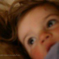 petite fille encore endormie, les yeux dans le vague, curieuse et pensive